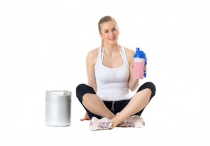 Young sporty woman sitting with protein shake