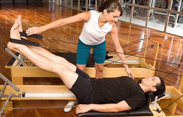 Girl assisting man during pilates