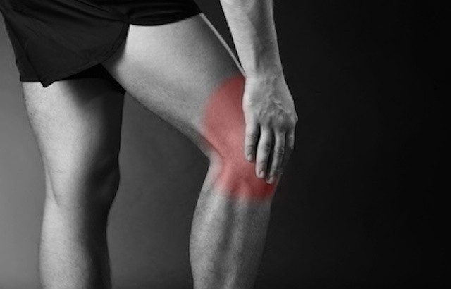 Young man with knee pain, on red background