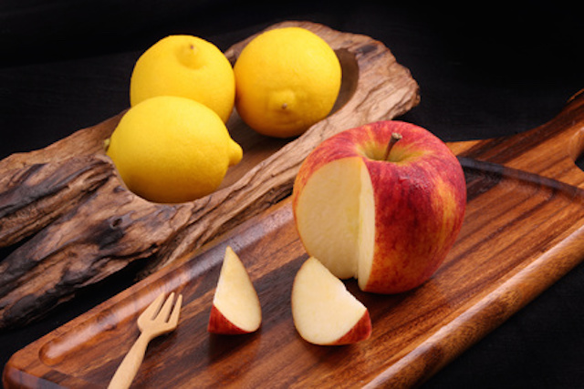 Cool organic fresh red apple on wooden tray with fork and cool lemons on classic tray isolated on black background