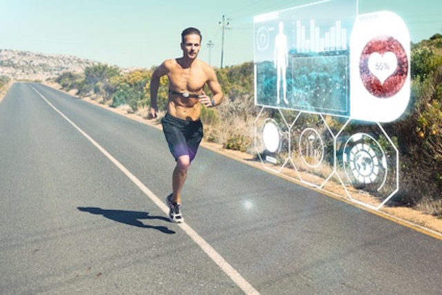 Athletic man jogging on open road with monitor