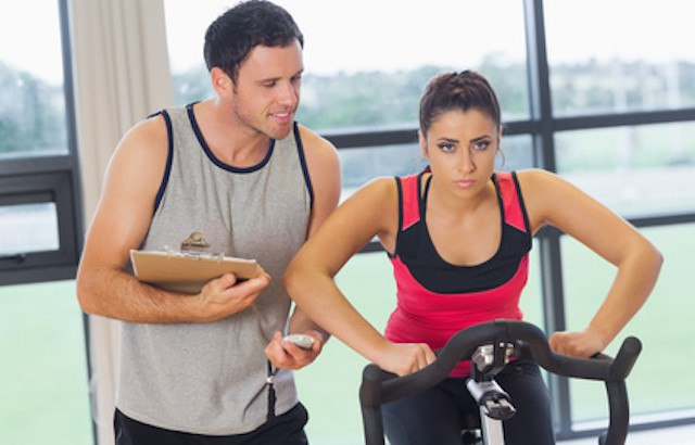 Male trainer watching woman work out at spinning class in gym