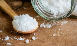 Sea salt and wooden spoon on wooden table