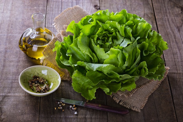 Butter lettuce and oil over rustic background